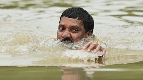 Chennai: A man moves to safe place from flooded Kotturpuram during heavy rains in Chennai on Wednesday. PTI Photo by R Senthil Kumar(PTI12_2_2015_000148A)