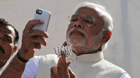 Narendra Modi displayed his party's symbol lotus, after having cast his vote. (AP Photo)