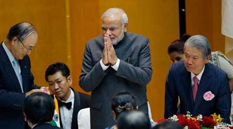 Prime Minister Narendra Modi greets business leaders after giving a speech and returning to his seat as Chamber of Commerce and Industry Chairman Akio Mimura. (Source: AP)