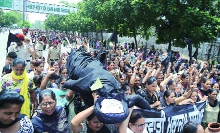 Anganwadi workers burn Tirath's effigy,demand approval ofpension