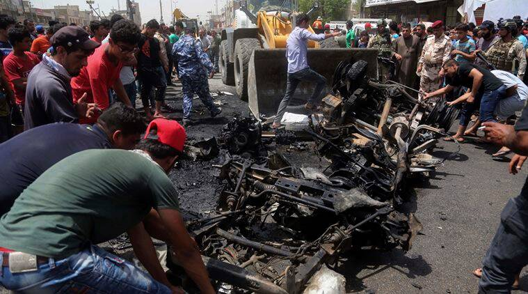 Civilians help a municipality bulldozer clean up while citizens inspect the scene after a car bomb explosion at a crowded outdoor market in the Iraqi capital's eastern district of Sadr City, Iraq, Wednesday, May 11, 2016. An explosives-laden car bomb ripped through a commercial area in a predominantly Shiite neighborhood of Baghdad on Wednesday, killing and wounding dozens of civilians, a police official said. (AP Photo/ Khalid Mohammed)