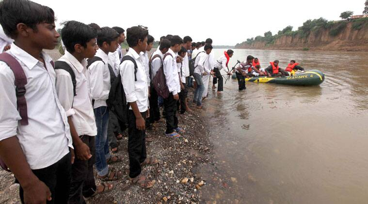 Students of villages in Sajanpura taluka watch the inflatable motor boat that will now ferry them dry, across the Hiran, on their way to school.  (Source: Express Photo by Bhupendra Rana)