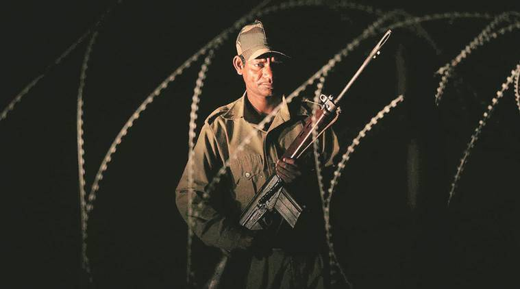 War zone: A security man keeps watch from behind barbed wire fencing outside a police station near the Bijapur Salwa Judum camp. The entire region lives on the edge with Naxal violence steadily growing in intensity and all of the government's moves invariably coming to a nought.