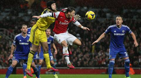 Chelsea goalkeeper Petr Cech, left punches the ball clear under pressure from Arsenal's Mesut Ozil during their English Premier League soccer match between Arsenal and Chelsea at the Emirates stadium in London (AP)