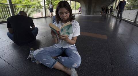 A girl reads a book along an elevated walkway during a protest in Bangkok, Thailand. ( Source: AP )