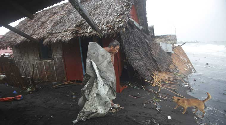 A Filipino man carries a dirty plastic sheet from his house after strong waves from Typhoon Hagupit battered a coastal village in Legazpi, Albay province, eastern Philippines on Monday. (Source: AP)
