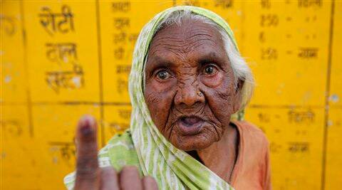 An elderly woman Kevali, 80, displays the indelible ink mark on her finger after casting her vote, outside a polling station in Allahabad. (AP)
