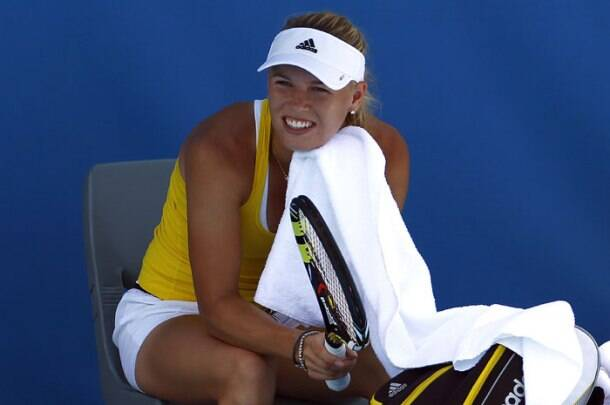 The Sun, the fun and the tan! Wozniacki takes a break during a training session at Melbourne Park (Reuters)
