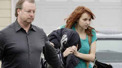 A woman believed to be Amanda Knox, center, is hidden under a jacket while being escorted from her mother's home to a car by family members in Seattle. (AP photo)