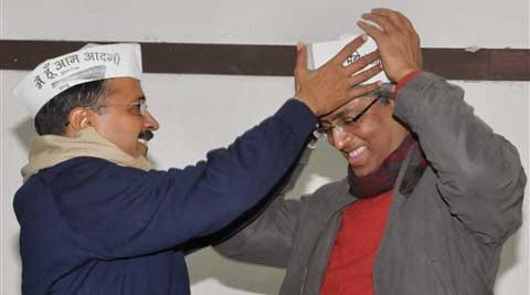 Delhi CM Arvind Kejriwal offers cap to Ashutosh who formally joined Aam Aadmi Party in New Delhi on Saturday. (PTI)
