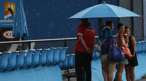 Spectators shelter from the rain as the rain stop play at the Australian Open tennis championship in Melbourne (AP)