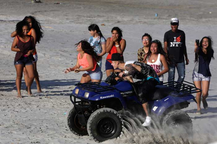 Thrilled to have an audience, the pop star shows off some stunts on the sand. (AP)