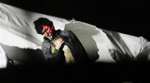 In this Friday, April 19, 2013 Massachusetts State Police file photo, 19-year-old Boston Marathon bombing suspect Dzhokhar Tsarnaev, bloody and disheveled with the red dot of a sniper's rifle laser sight on his head, emerges from a boat at the time of his capture by law enforcement authorities in Watertown.