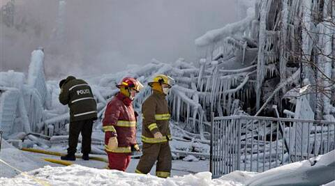 Police and firefighters survey the damage after a fatal fire at a seniors residence in L'Isle-Verte, Thursday. (AP)