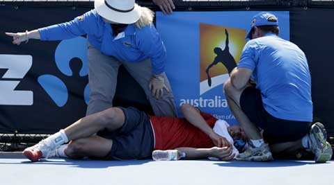 Frank Dancevic of Canada lies on the court after collapsing during his first round match against Benoit Paire of France as temperatures topped at 43 C (108 F) at the Australian Open tennis championship in Melbourne (AP)