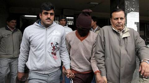 Police officials escort an accused in the gang rape of a 51-year-old Danish tourist as they walk out of a court in New Delhi. (AP)