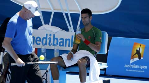 Novak Djokovic sips fluids during a practice session in searing heat in Melbourne (AP)