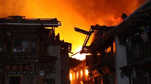 Firefighters work on roofs of buildings while a fire ravages ancient Dukezong town in Shangri-la county, in southwestern China's Yunnan province. (AP)