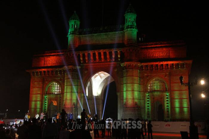 People gather at the Gateway of India as it is illuminated with the dynamic special effects of the LED lights in Mumbai. (IE Photo: Dilip Kagda)