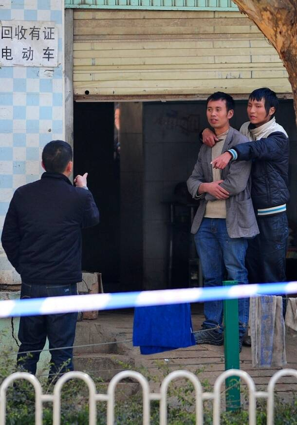 A man is held hostage on a street at a electric bicycle maintenance shop as police stands by in Kunming