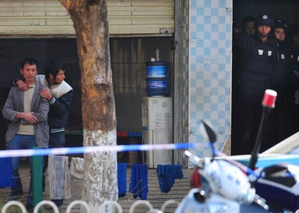 A man is held hostage at an electric bicycle maintenance shop as police officers stand by in Kunming