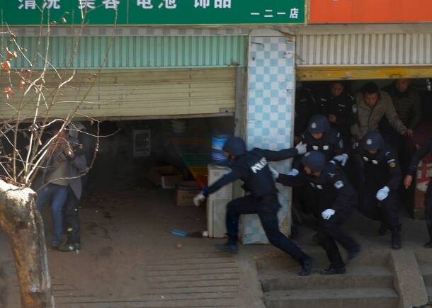 Police officers run into an electric bicycle maintenance store to rescue a hostage in Kunming