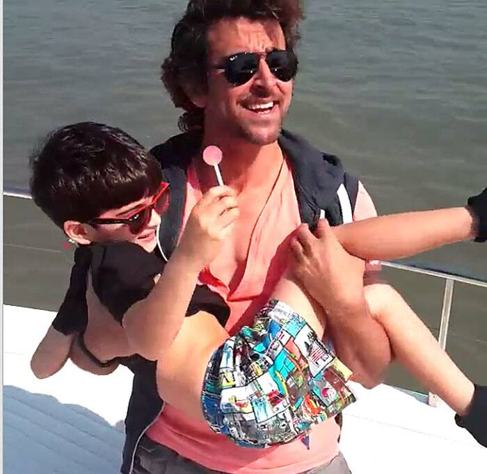 Hrithik Roshan carries his son, who was busy eating a lollypop. (Instagram)