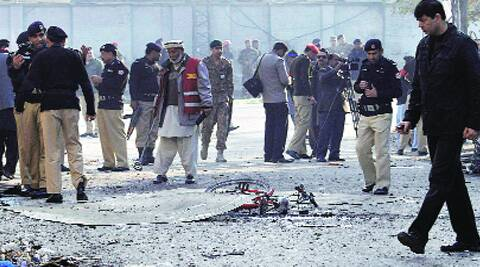 Civilians gather at the site of the suicide bombing in Rawalpindi Monday. AP