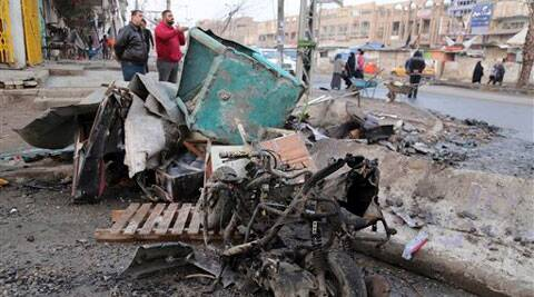 Civilians inspect the aftermath of car bomb attack in Baghdad on Tuesday. (AP)