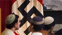 Visitors stand in front of a flag with the Nazi swastika at Yad Vashem's Holocaust History Museum in Jerusalem. (Reuters)