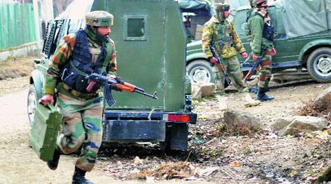 Security personnel rush to take positions near the house where the militants were holed up at Dooru in Sopore, on Monday. (PTI)