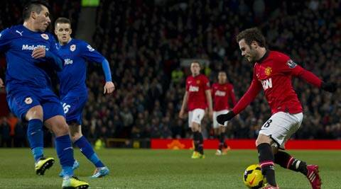 Manchester United's Juan Mata, right, keeps the ball from Cardiff City's Gary Medel, left, and Craig Noone, second left, during their English Premier League soccer match at Old Trafford Stadium (AP)