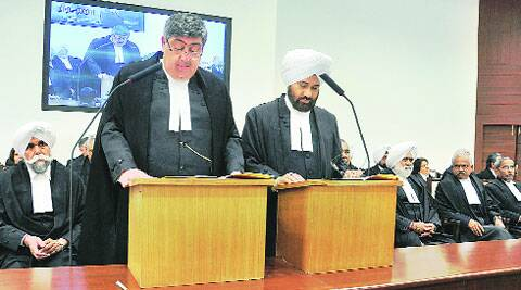 Chief Justice of Punjab and Haryana High Court, Sanjay Kishan Kaul, administers oath to Justice Kuldip Singh (right) in Chandigarh on Friday. (Express)