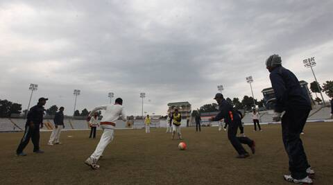 Members of the Karnataka team play football on the fourth day of the semifinal against Punjab. Only 36 overs were bowled on Tuesday (IE Photo Jasbir Malhi)