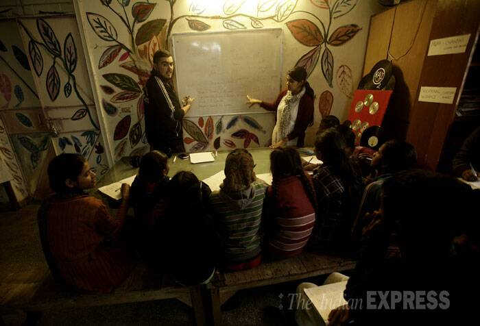 "A group of young kids, from a slum colony called the Jagdamba area, behind Apeejay School, sit in rapt attention in class as their teacher takes them through three-and four-letter words. This is Jack Todd's second stint as a teacher in Delhi, and Khirki Extension has been his home both times. A volunteer for the NGO Swechha, Todd lives in R Block. ""I feel safer in Khirki than I do in parts of south London… and that's something,"" he says. (IE Photo: Praveen Khanna)"