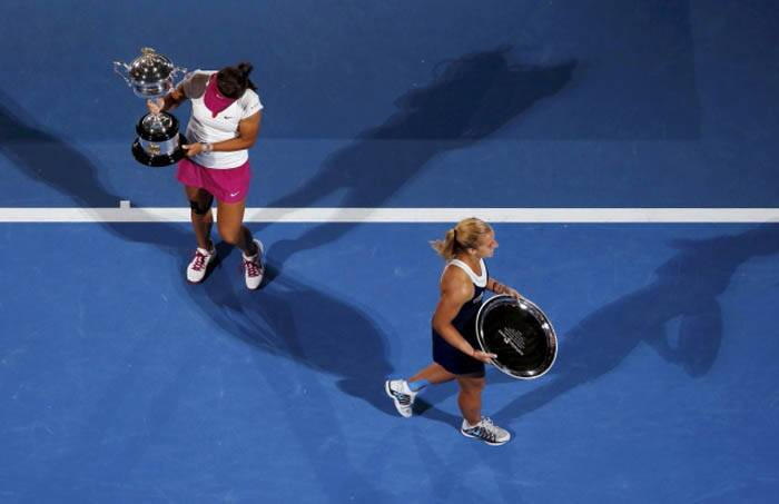 Li Na (L) of China looks at the Daphne Akhurst Memorial Cup as Dominika Cibulkova of Slovakia walks away after their women's singles final match at the Australian Open 2014 tennis tournament in Melbourne January 25, 2014. REUTERS/David Gray (AUSTRALIA  - Tags: SPORT TENNIS)