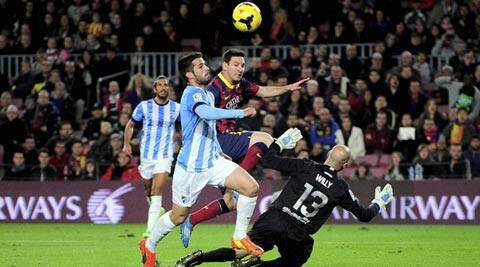 Barcelona's Lionel Messi, from Argentina, center, duels for the ball with Malaga's Flavio, second left, and goalkeeper Willy Caballero during a Spanish La Liga soccer match at the Camp Nou stadium (AP)