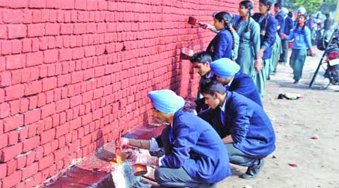 Students paints the wall of SCD Government College  in Ludhiana on Saturday. Gurmeet Singh