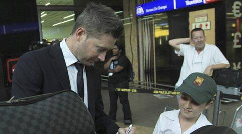Australia's cricket captain Michael Clarke, left, signs a small cricket bat for unidentified fan during their arrival at OR Tambo International Airport in Johannesburg, South Africa (AP)