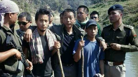 The released men (pictured holding sticks) with Mizoram Police personnel near Silsury (Express photo)