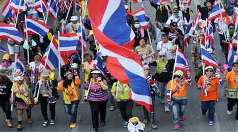 Thai anti-government protesters carry national flags during a march in Bangkok, Thailand Thursday, Dec. 19, 2013. Thailand's anti-government protesters returned to Bangkok streets Thursday, turning one of the capital's major intersections into a lunchtime picnic spot in their bid to force Prime Minister Yingluck Shinawatra from office. (AP Photo)