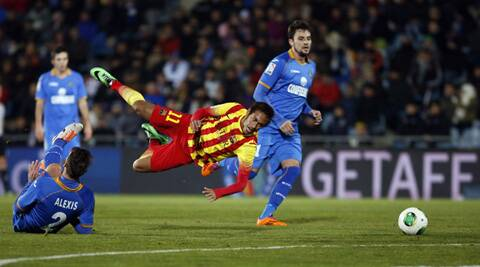 Barcelona's Neymar (C) falls as he is tackled by Getafe's Alexis Ruano (L) during their Spanish King's Cup soccer match (Reuters)