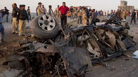 Pakistani investigators look at a vehicle destroyed by a bombing in Karachi, which killed a senior police officer known for arresting dozens of Pakistani Taliban. (AP)
