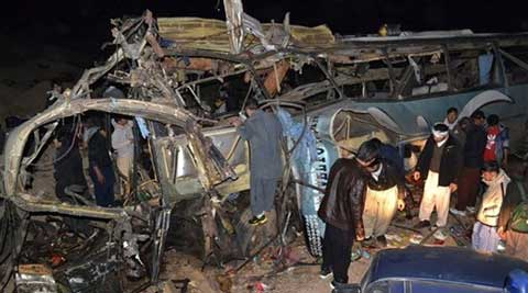 People look at the wreckage of a passenger bus destroyed in a bomb blast in the Mastong district, near Quetta, on Tuesday.