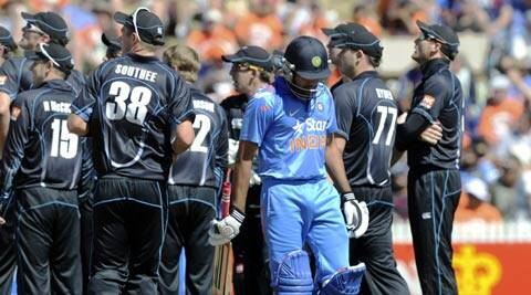 Rohit Sharma walks out for 79 as the New Zealand team watch the replay of the dismissal on the big screen (AP)