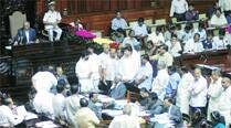 Opposition leaders protest in the Assembly well to demand handover of the Mallikarjuna Bande case to the CBI, at the Vidhana Soudha in Bangalore Monday.