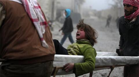 A boy reacts as he is carried on a stretcher at a damaged site after what activists said was heavy shelling by forces loyal to Syrian President Bashar Al-Assad. (Reuters)