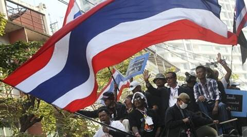 Anti-government protesters with national flags gather in Bangkok on Thursday.