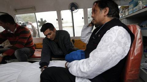 Shashi Tharoor and Sunanda's son Shiv Menon with her body at AIIMS in New Delhi on Saturday. (PTI Photo)