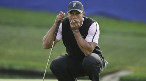 Tiger Woods examines his putt while waiting for his playing partners on the 18th green of the South Course at Torrey Pines during the first round of the Farmers Insurance Open (AP)